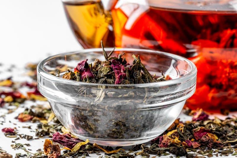 E 茶壶用在白色背景的异乎寻常的绿茶用疏散干茶 免版税库存图片