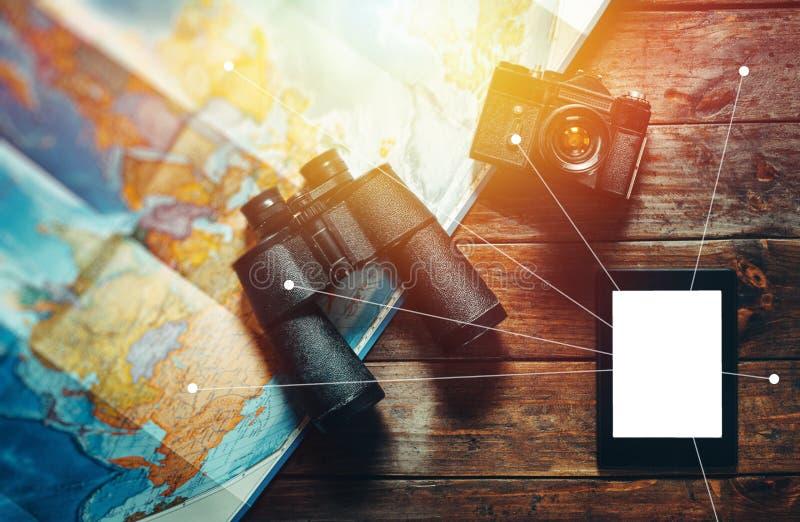 E 葡萄酒影片照相机、地图和双筒望远镜在木表,平的位置点上 免版税库存图片