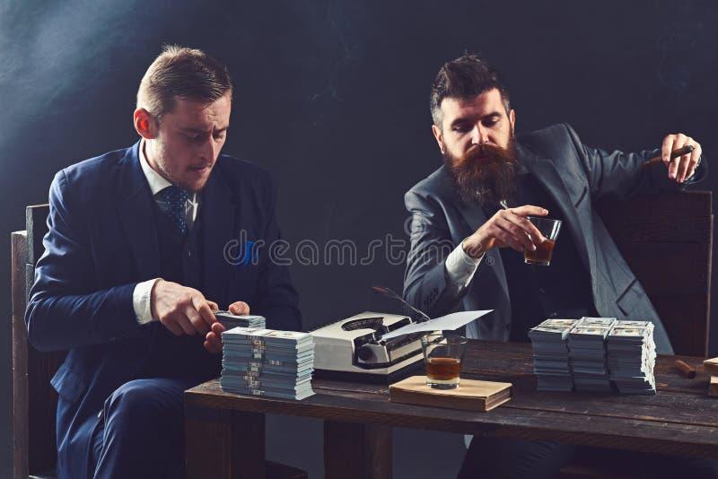 E 计数现金金钱的商人 写财政报告的商务伙伴 做生意 图库摄影