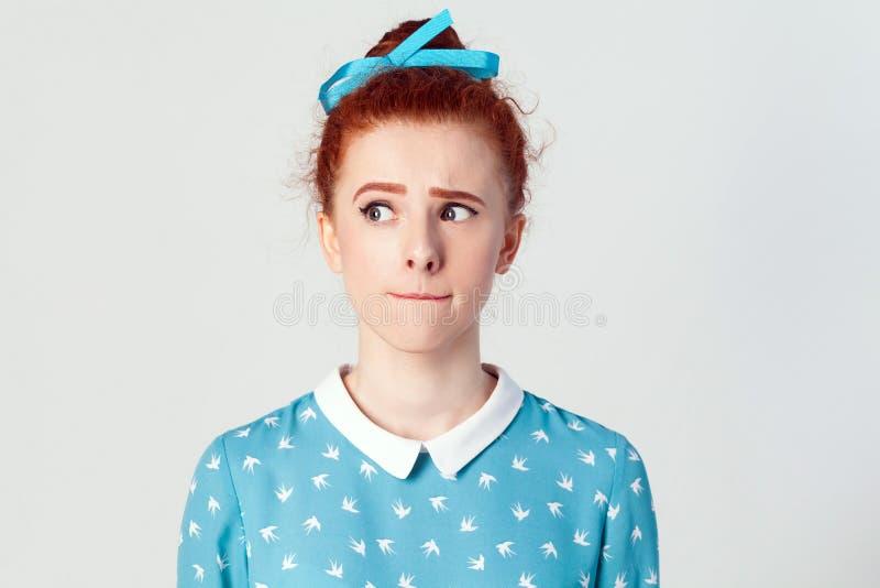 E 让我认为 被隔绝的演播室在逗人喜爱的红头发人女孩灰色背景射击了有看起来斜向一边和计划的某事 库存图片
