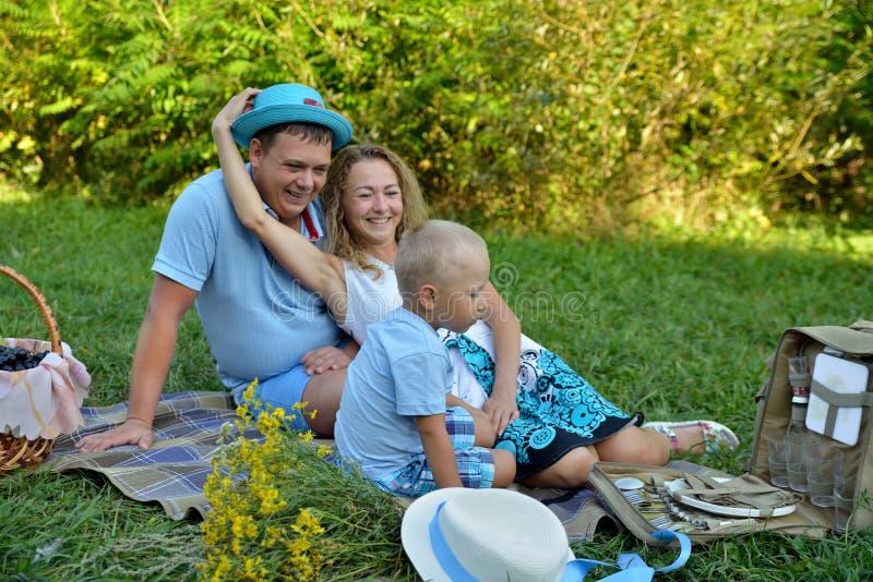 E 野餐本质上在一个夏日 妈妈和爸爸妇女的帽子的,微笑的看看他的小儿子本质上 免版税库存图片