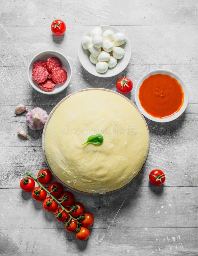 E 面团用香肠、西红柿酱、大蒜和无盐干酪 免版税图库摄影