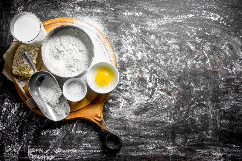 E 面粉用蜂蜜、牛奶和鸡蛋在切板 库存照片