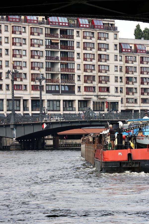 E 驾驶河的小船 在背景中桥梁和居民住房 免版税库存照片