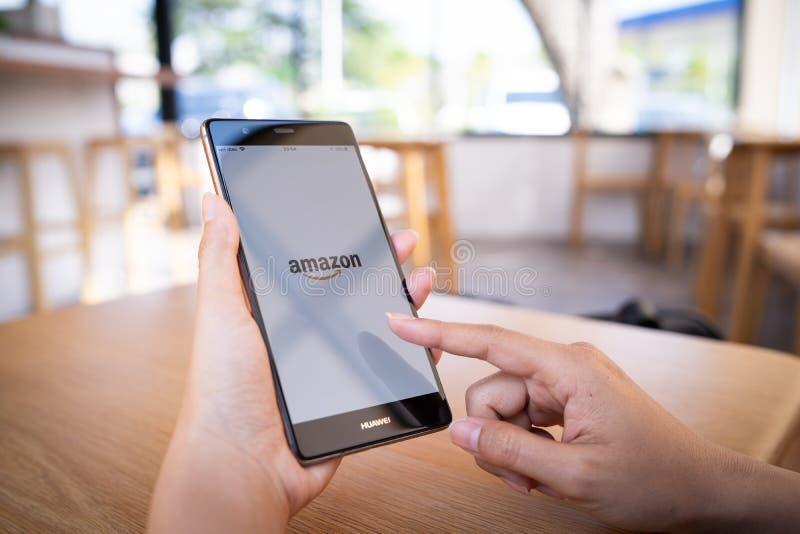 E 19,2019:举行有亚马逊应用程序的妇女手华为 免版税库存图片