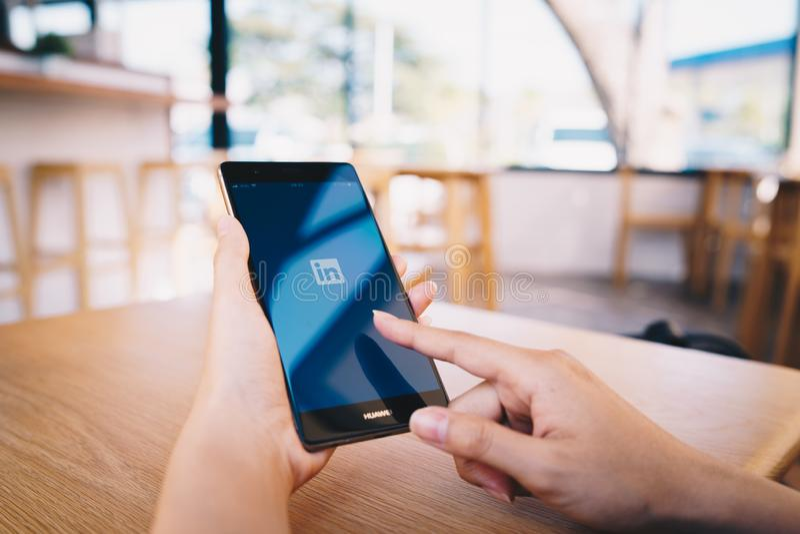 E 19,2019:拿着有Linkedin应用的妇女华为手机在屏幕上 Linkedin?a 库存照片