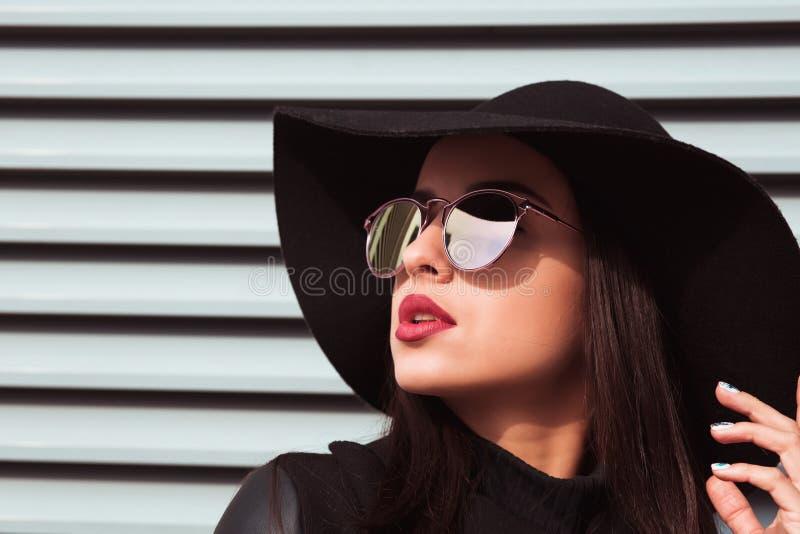 Закрытый портрет молодой модной модели носит шляпу и солнцезащитные очки Женщина позирует на заднем плане, сидя на заднем плане,  стоковое фото