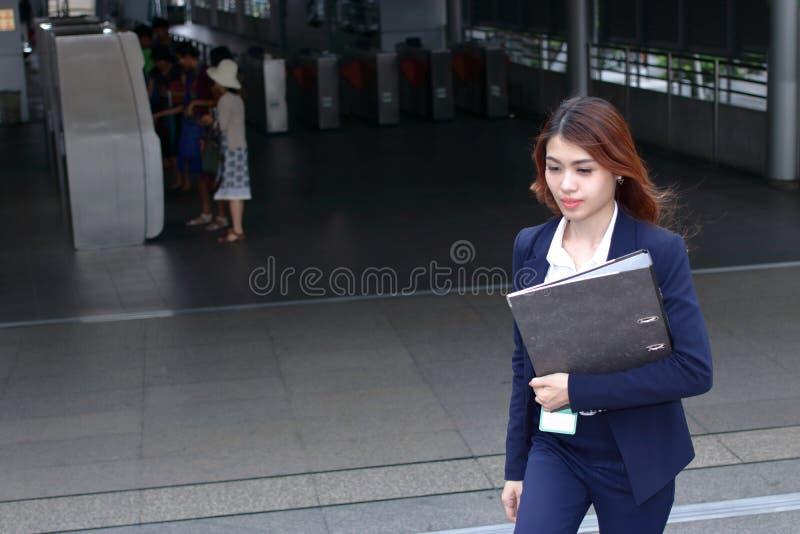 Вид на уверенную молодую азиатскую бизнесменку, которая поднимается по лестнице у входа на железнодорожный вокзал на заднем плане стоковое изображение