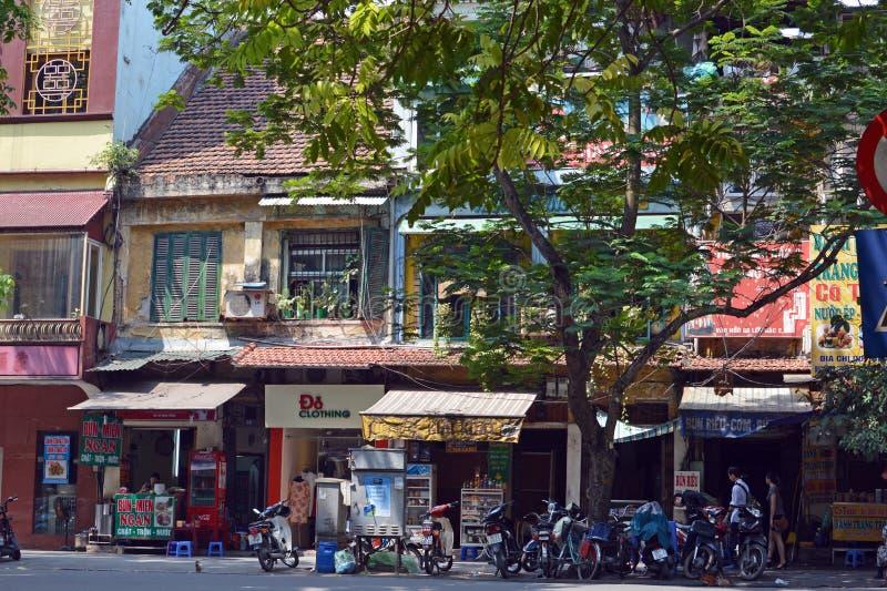 Вьетнам - Ханой - Типичная уличная сцена - Ряд магазинов на дереве, выстроенных на проспект с припаркованными снаружи скутерами стоковые изображения