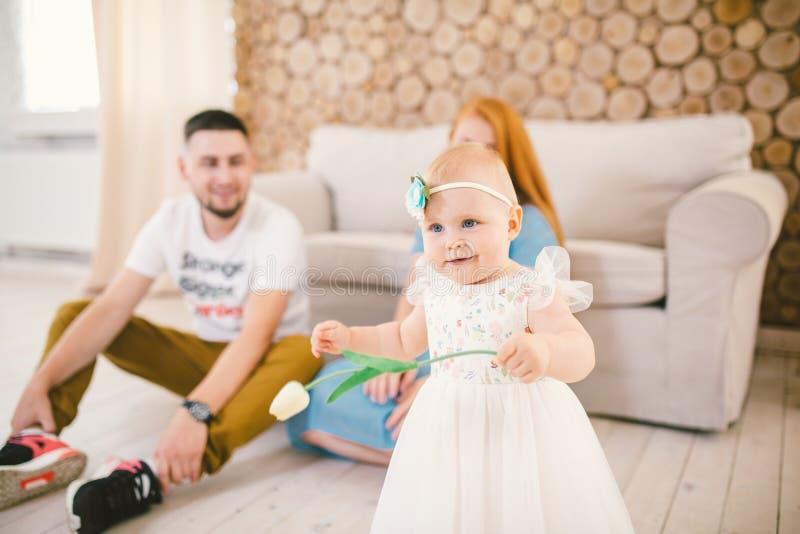 Молодая семья сидит на полу возле дивана, маленькая дочь блондинки одного года учится ходить в белом платье против стоковые фото