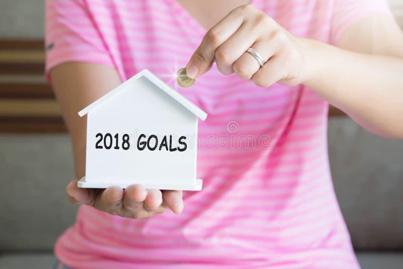 Цели на 2018 год: женщины-ручки кладут монеты в копилку, экономят деньги, покупают дом, G стоковые фото