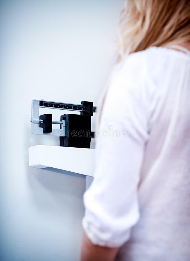 Женщина в клинике проверяет свой вес стоковые изображения