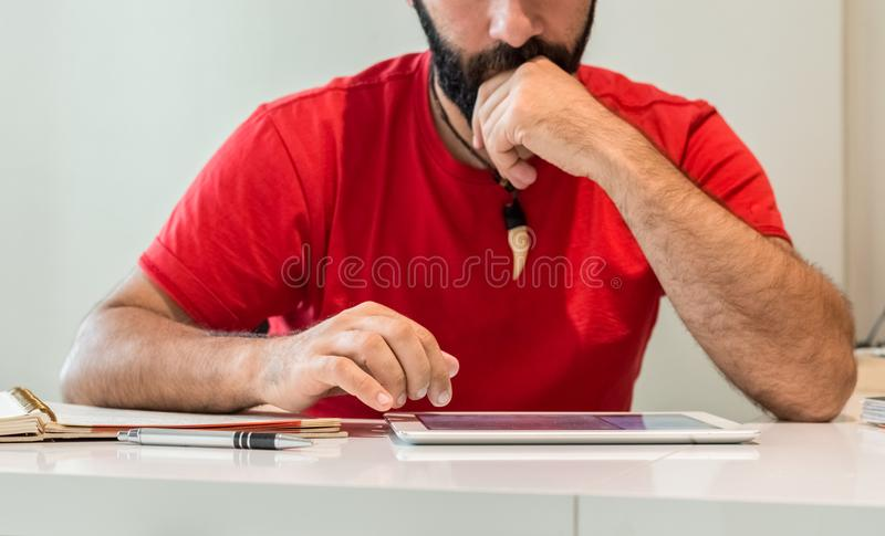 Молодой кавказский бородатый мужчина с красной рубашкой, с таблеткой в огне стоковые фото