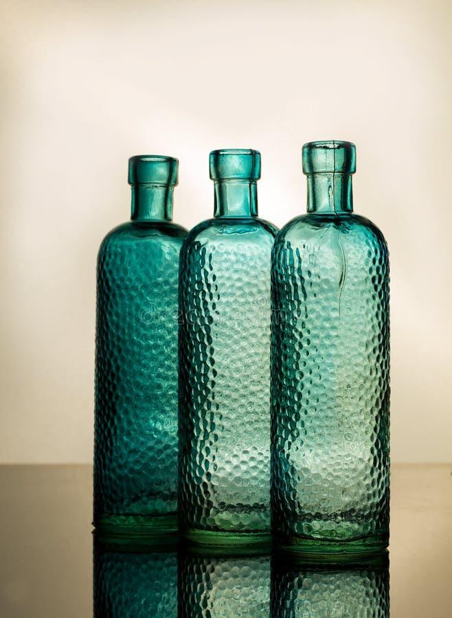 Синие антикварные стеклянные бутылки в заднем свете стоковые изображения