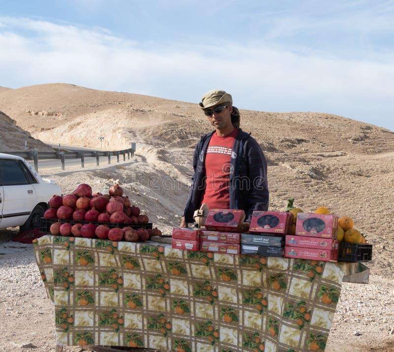 Бедуин продает свежие и сушеные фрукты туристам на проспектной площадке возле Митцпе Ерихо в Израиле стоковое фото rf