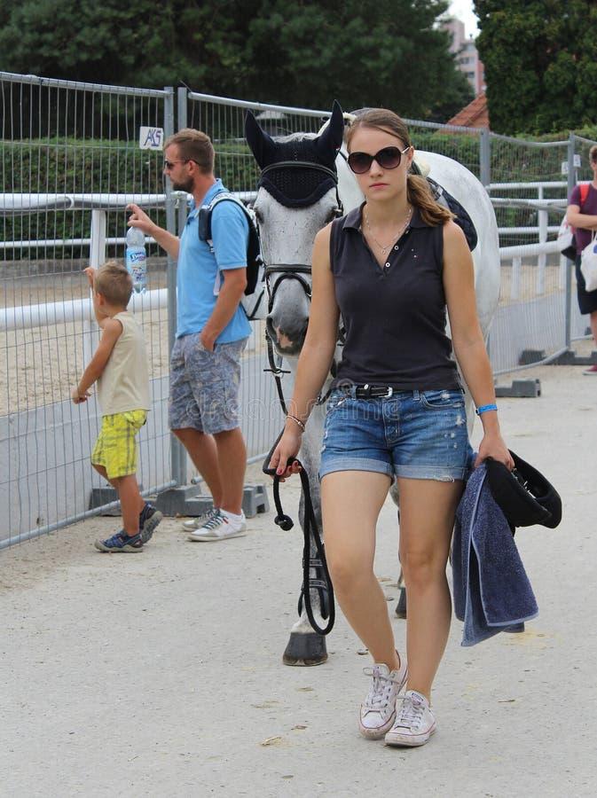 Девушка, идущая на лошади после соревнований по прыжкам с парашютом стоковая фотография