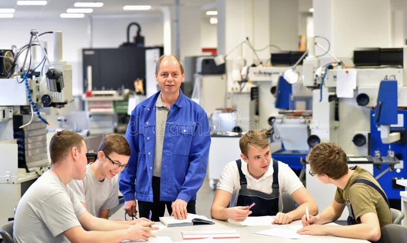 Группа молодых людей, прошедших профессионально-техническую подготовку, с учителем стоковое изображение rf