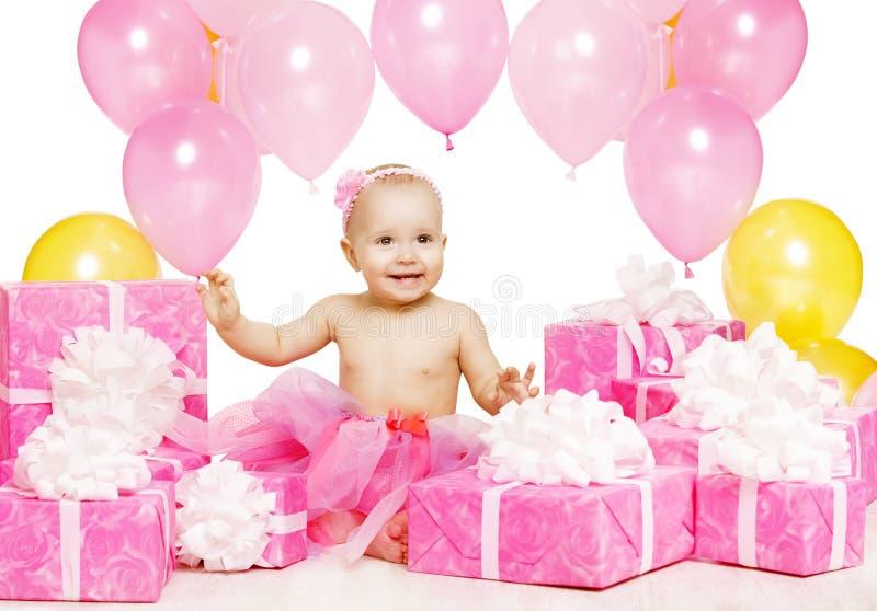 Девочка с розовыми подарочными коробками, ребёнок празднует день рождения стоковая фотография