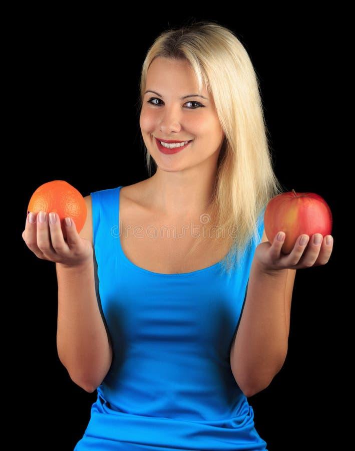Миленькая дает яблоко и оранжевый стоковая фотография