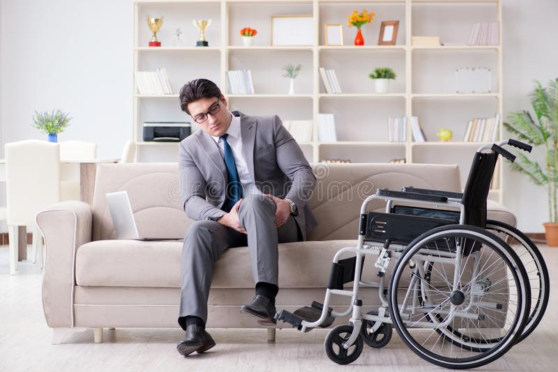 Бизнесмен с инвалидными колясками, работающий дома стоковая фотография