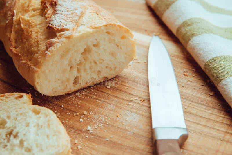 Свежий нарезанный багет с ножом на резиновой доске стоковое фото rf