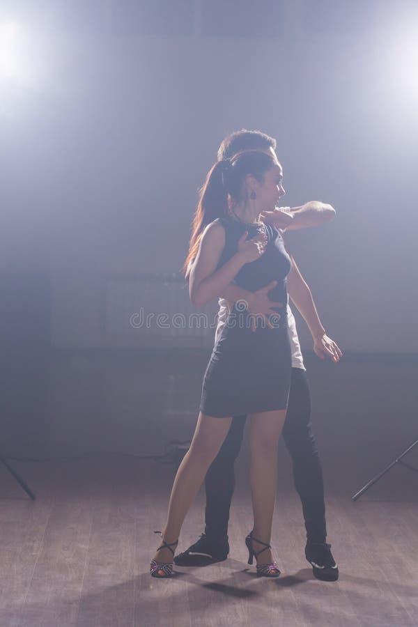 Молодая пара танцует социальный дансе кизомба, бачата, семба или тараксия в танцевальном классе фон стоковые фото