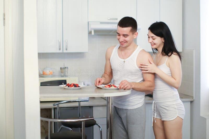 Муж и жена готовят завтраки утром на кухне, в футболках стоковая фотография