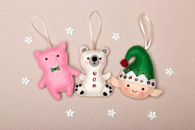 Комплект украшений рождественской ёлки, свиньи, полярного медведя, эльфа, ручной работы из войлока на бежевом фоне снежинками стоковые фото