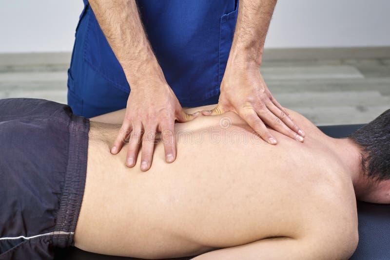 给后面按摩的生理治疗师 按摩脊柱治疗者,整骨疗法,手工疗法,针压法 图库摄影