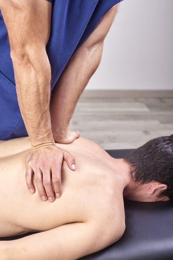 给后面按摩的生理治疗师 按摩脊柱治疗者,整骨疗法,手工疗法,针压法 免版税库存照片