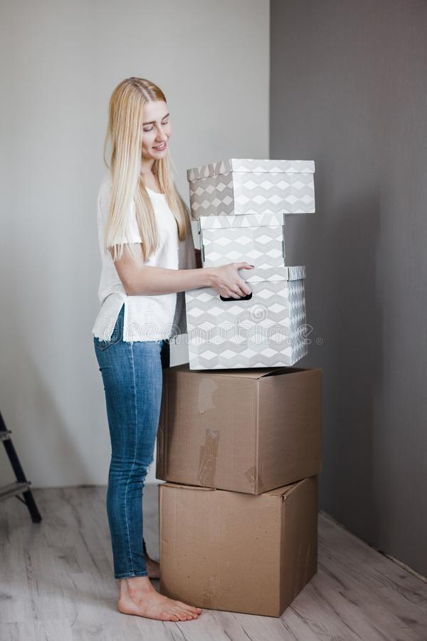 搬入新的公寓的年轻女人拿着有财产的纸板箱 E 库存照片