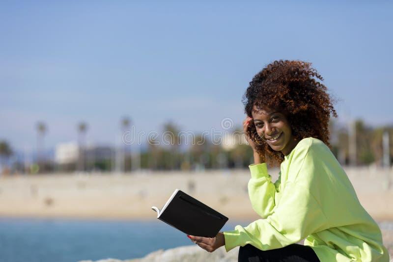 年轻卷曲非洲的妇女侧视图坐拿着书的防堤,当微笑和看户外时 免版税库存照片