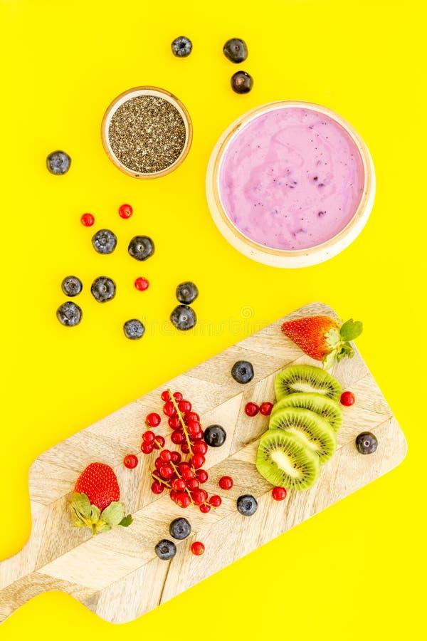 E Acai smoothiebunke nära skärbräda med nya frukter, bär, chiafrö på guling royaltyfria foton