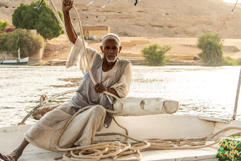 E 05 2018 alter Nubian Mann, der auf Felucca-Bootsdeck sitzt und hinunter Nile River segelt stockfotografie