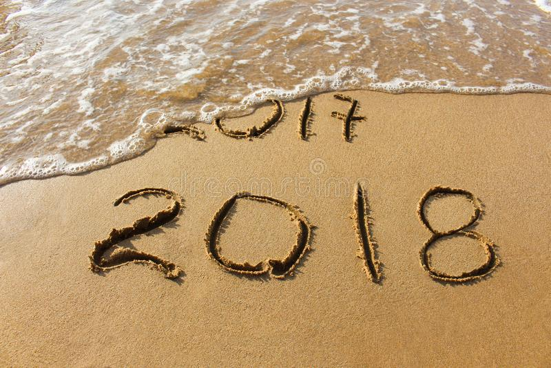 2017 e 2018 anni scritti sul mare della spiaggia sabbiosa immagine stock libera da diritti