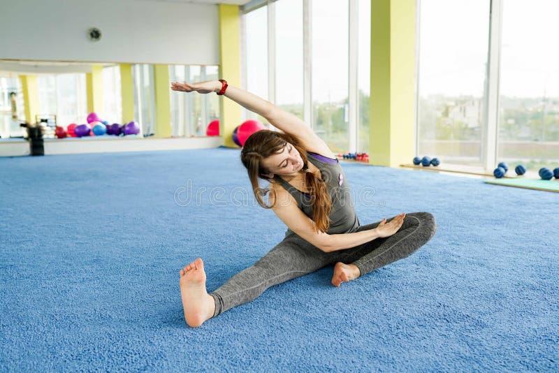 E Attraktive junge Frau, die auf dem Boden in der Turnhalle trainiert und sitzt stockbild