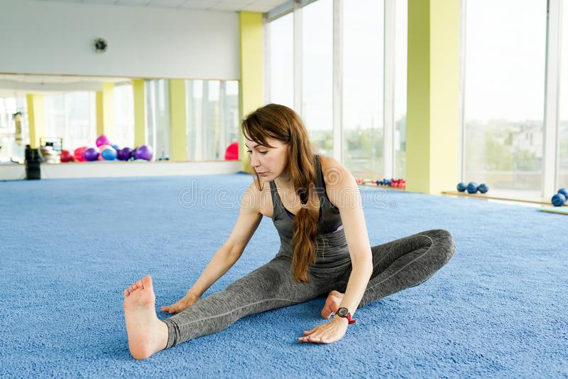 E Attraktive junge Frau, die auf dem Boden in der Turnhalle trainiert und sitzt Konzept des gesunden Lebensstils stockfotos