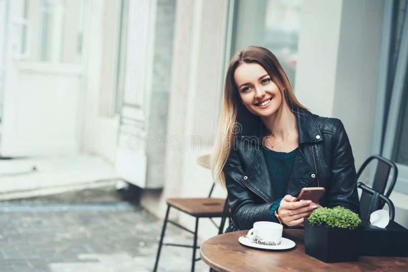 E Attraktive junge Frau mit einem Lächeln, das und schreibenden schnellen Mitteilung des Cafés in der im Freien sitzt stockfotografie