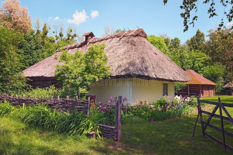 E Aturdir la opinión del paisaje de la casa de la arcilla con el jardín imagen de archivo