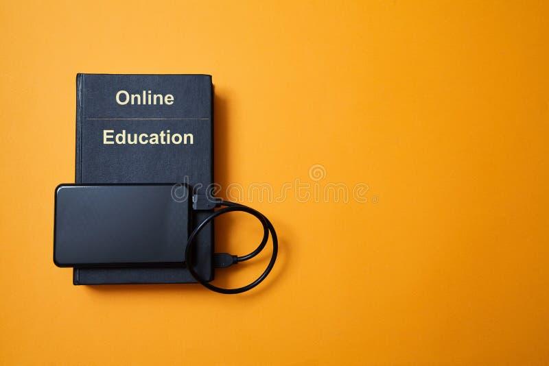 E-bibliotheek E-learning, online onderwijs of e-book Webinar, internetcursussen Boek en harde schijf op gele achtergrond stock afbeelding