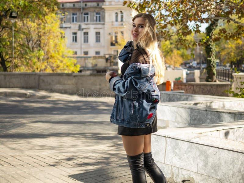 E blondemeisje met stromend haar in een jeansjasje die zich op de straat tegen de achtergrond van gele bomen bevinden royalty-vrije stock fotografie