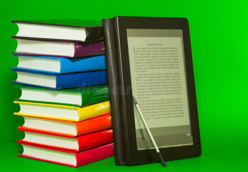 E-boek lezer met stapel afgedrukte boeken stock fotografie