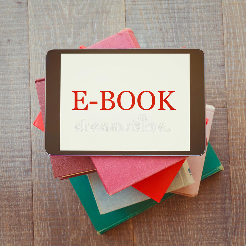E-book library concept with digital tablet and books. On wooden table royalty free stock images