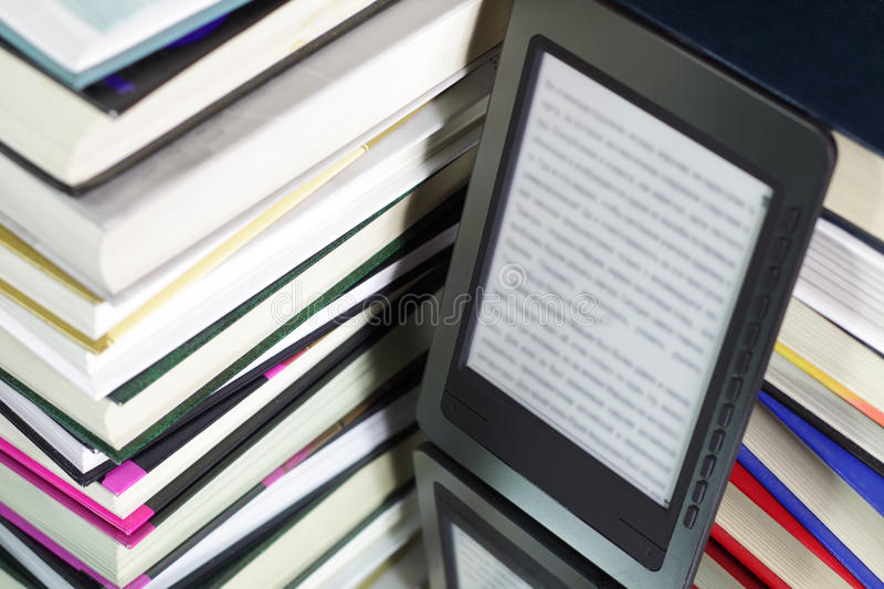 E-book reader. Against the background of a stack books stock photography