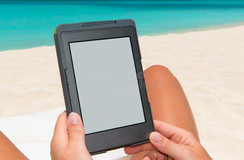 E-book reader. At the beach royalty free stock image