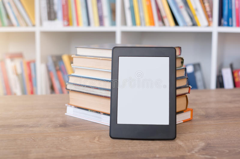 E-book reader and bookshelf stock images