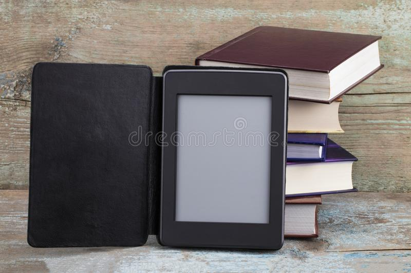 E-book reader device on desk in library. Alternative for traditional books.  stock image