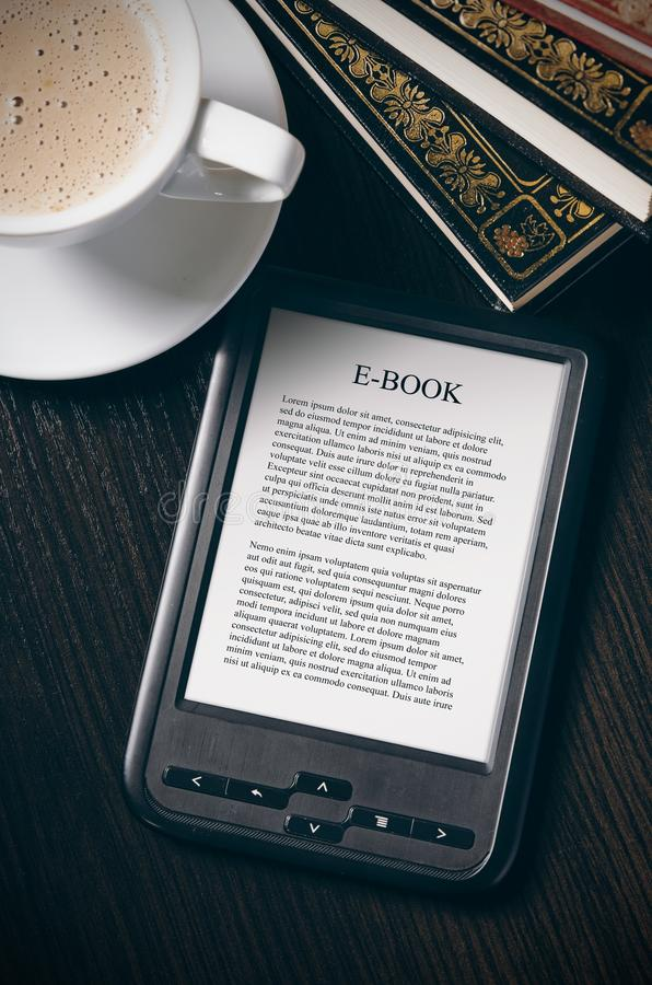 E-book reader device on desk in library. Alternative for traditional books royalty free stock images