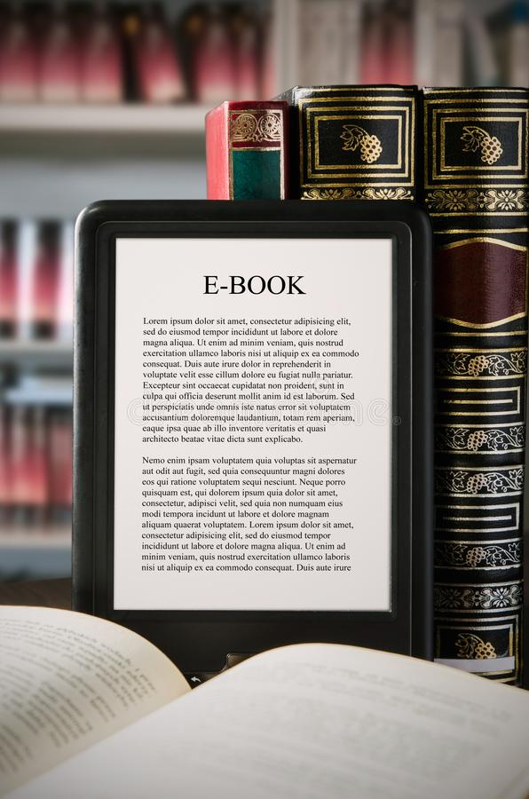 E-book reader device on desk in library. Alternative for traditional books stock photo