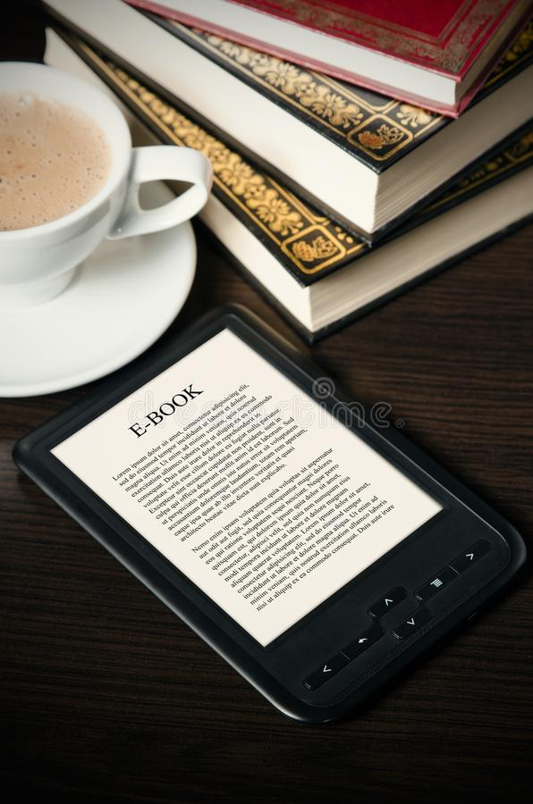 E-book reader device on desk in library. Alternative for traditional books royalty free stock photo